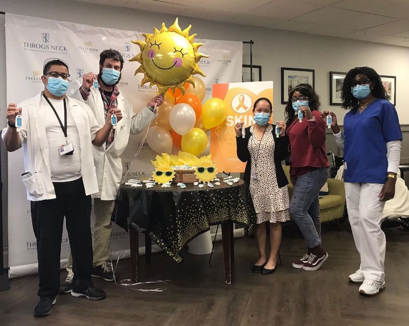 Small group of employees around a table with sunshine balloon